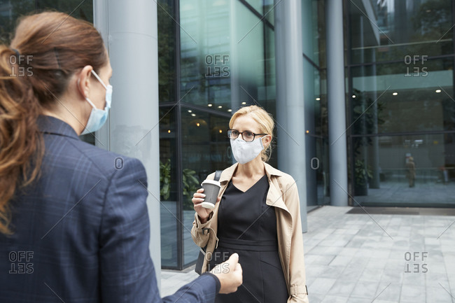 Women wearing face mask while talking against office building