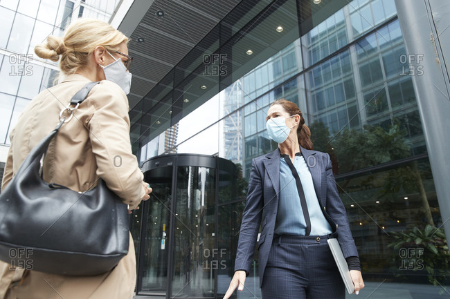 Mature women wearing face mask talking while standing against office building