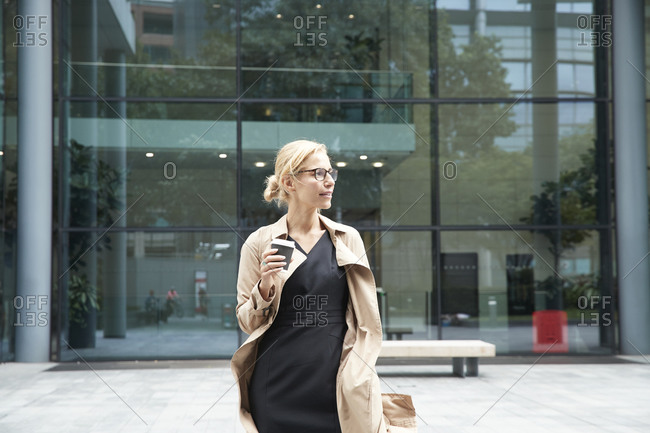 Woman holding coffee cup while standing against office building