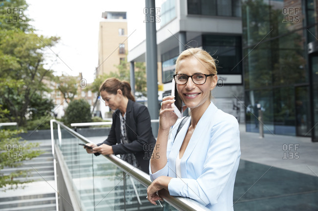 Smiling woman talking on mobile phone while colleague standing in background at city