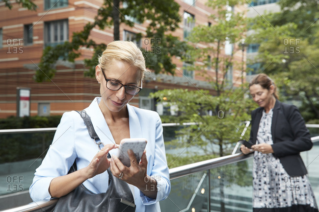 Woman using mobile phone while colleague standing in background at city