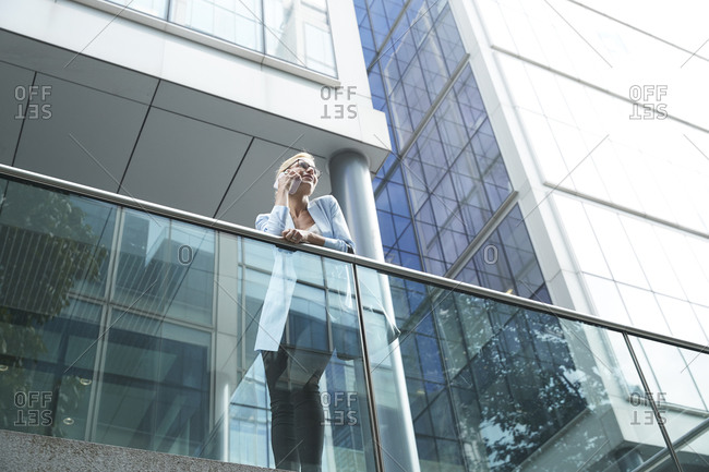 Woman talking on mobile phone while leaning on railing against building