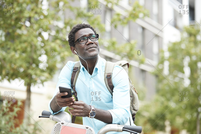Man looking up while listening music through earphones standing with bicycle in city