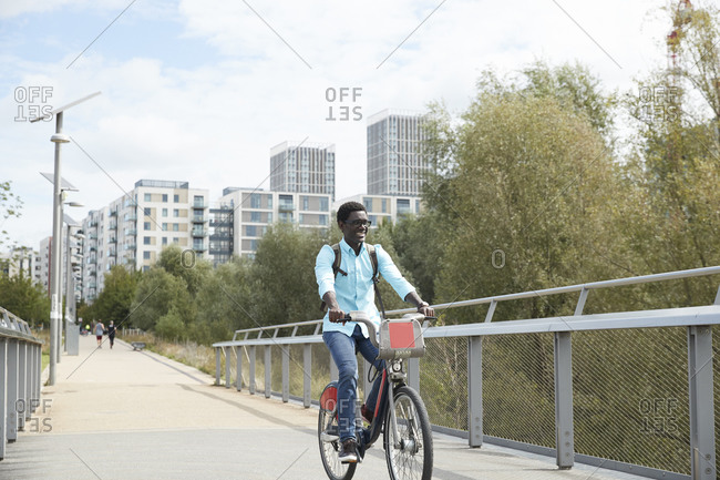 Smiling man commuting on bicycle in city