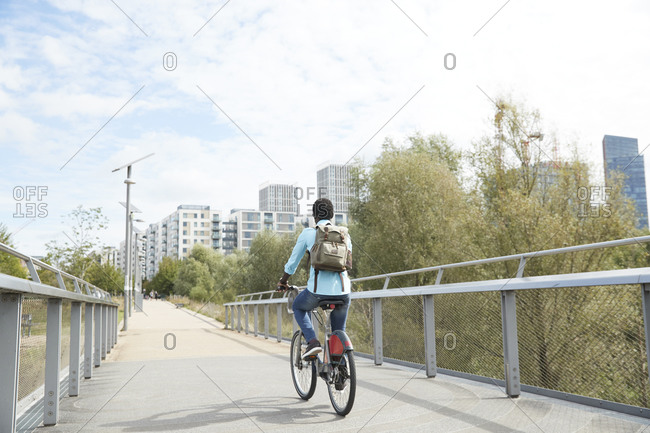 Mature man commuting on road with bicycle in city