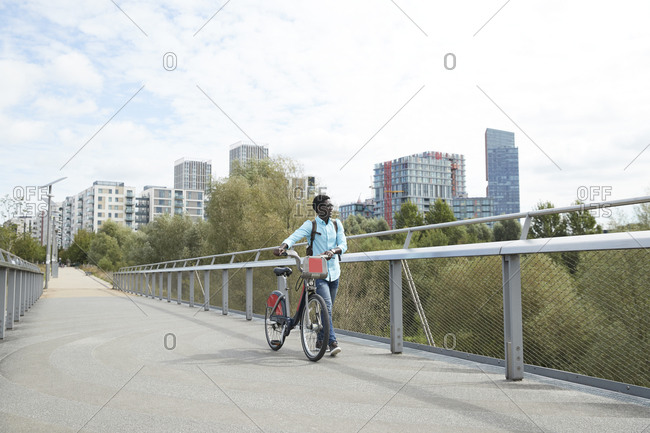 Man walking with bicycle on road against sky in city