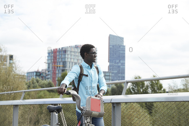 Man looking away while walking with bicycle against sky in city