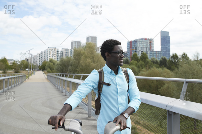 Smiling man looking away while walking with bicycle against sky in city