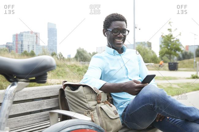 Smiling man using smart phone listening music through earphone sitting on bench in city