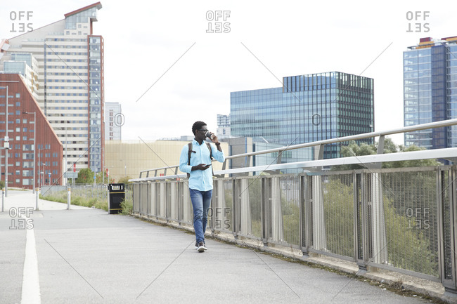 Mature man drinking coffee while holding smart phone walking on footpath in city