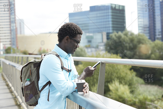Man using smart phone while leaning on railing in city