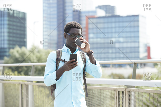 Mature man drinking coffee while using smart phone standing in city