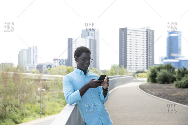 Mature man smiling while using smart phone standing on footpath in city