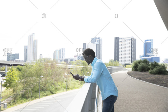 Mature man using smart phone standing on footpath in city