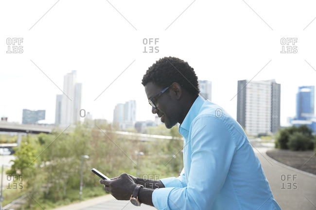 Man using smart phone standing on footpath in city