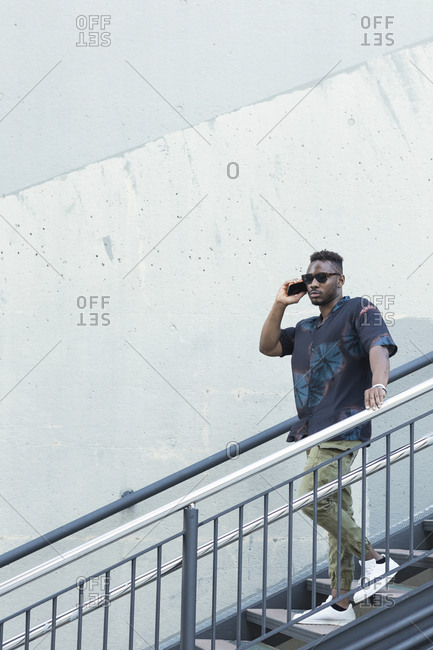 Young man moving down on steps by wall while talking on smart phone