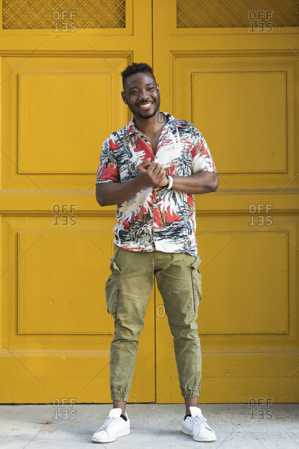 Happy young man with hands clasped standing against closed yellow doors