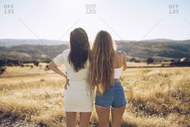 Female friends looking at view while standing on grassy field against sky during sunny day