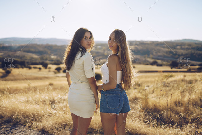 Beautiful female friends standing on grassy field against sky on sunny day