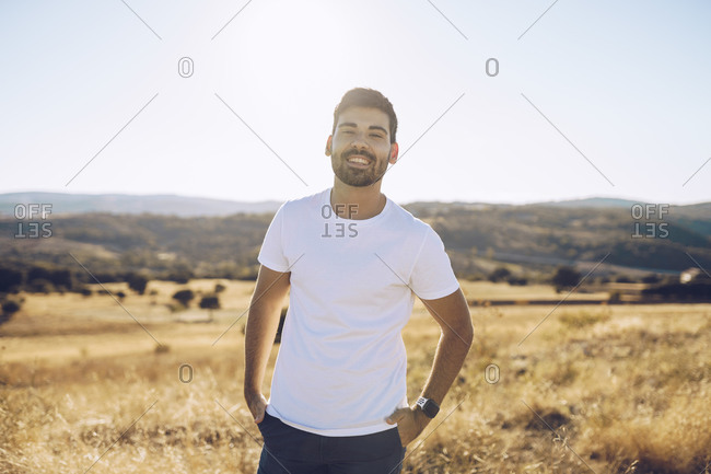 Smiling young man standing with hands in pockets on field against sky during sunny day