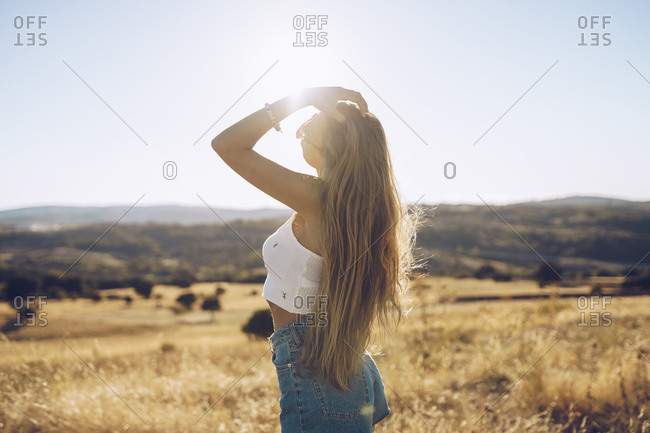 Young woman with hand in hair standing on field against sky during sunny day