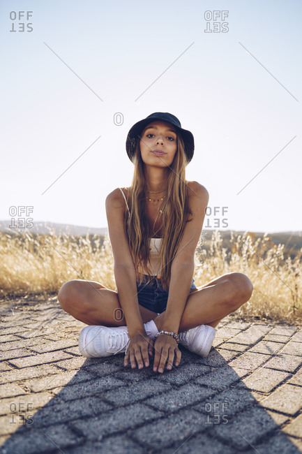 Young woman sitting on footpath against sky on sunny day