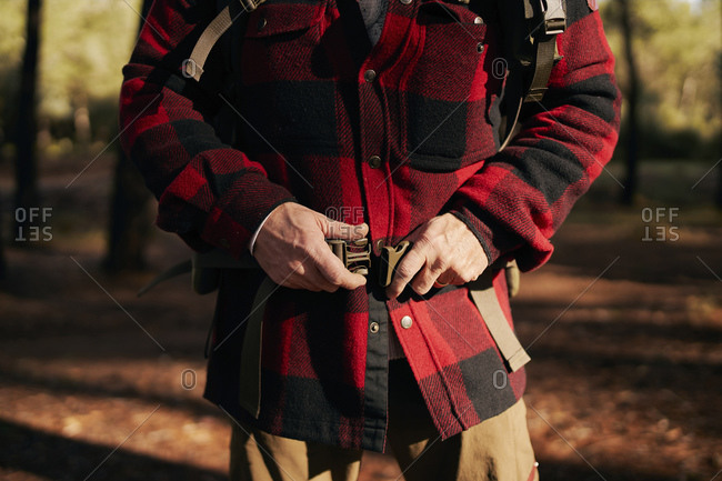 Midsection of bush crafter fastening belt while standing in forest