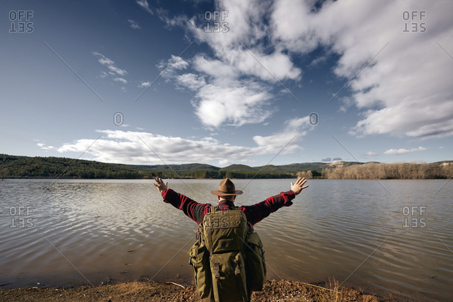 Bush crafter looking at lake with arms outstretched while standing in nature
