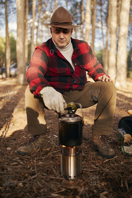 Bush crafter cooking on camping stove while sitting in forest