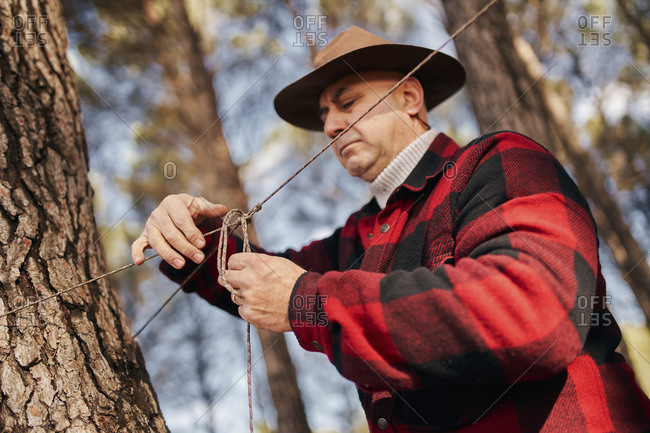 Bush crafter tying rope to tree bark in forest