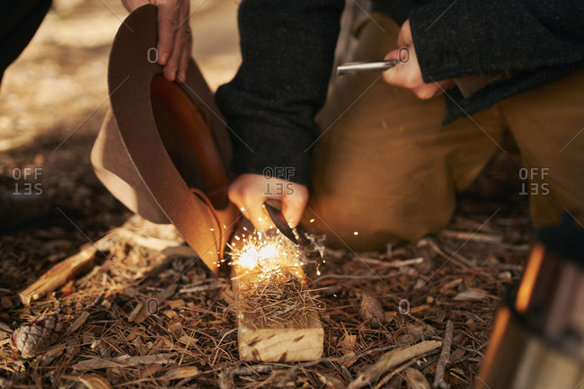 Midsection of bush crafters enlighten fire in forest