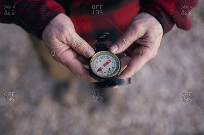Cropped image of bush crafter holding navigational compass while hiking