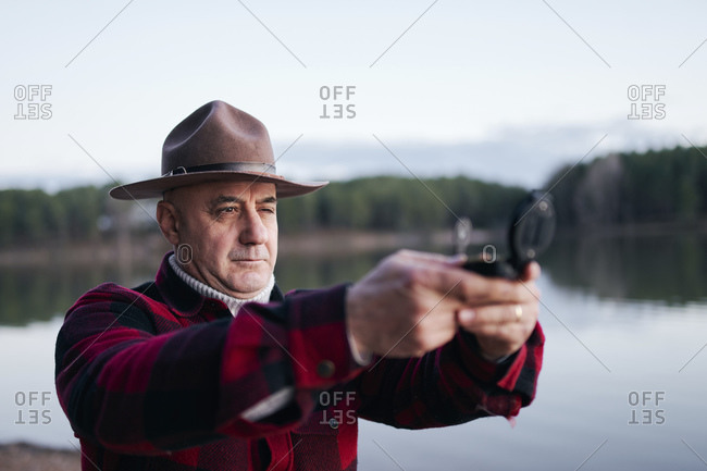 Bush crafter wearing hat holding navigational compass while standing against lake in forest