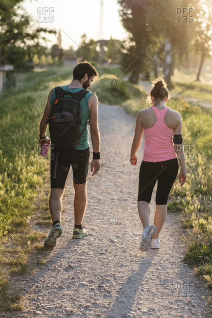 Active couple in sports clothing walking at park during sunset