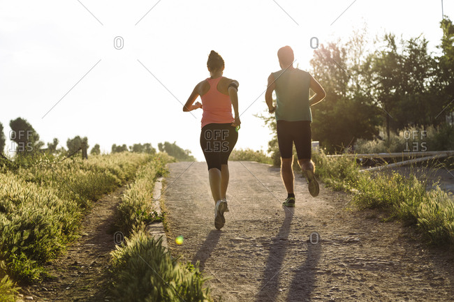 Fit young couple jogging in park during sunset
