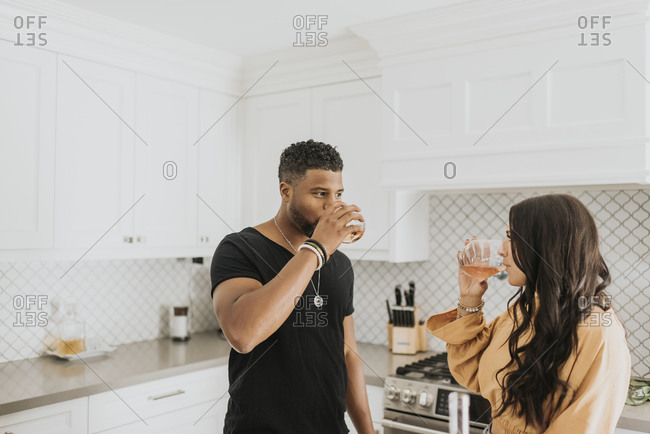 Couple drinking wine while standing in kitchen at home