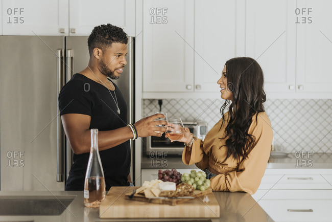 Couple toasting wineglass while standing in kitchen at home