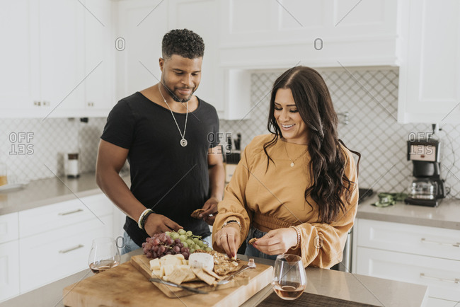 Couple eating food while standing in kitchen at home