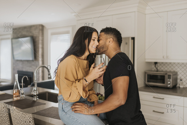Man kissing woman sitting on kitchen counter at home