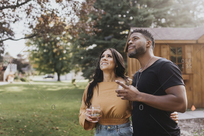 Man and woman with wineglass looking up while standing at backyard