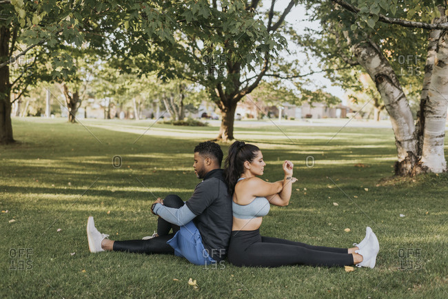 Couple stretching while sitting back to back at backyard