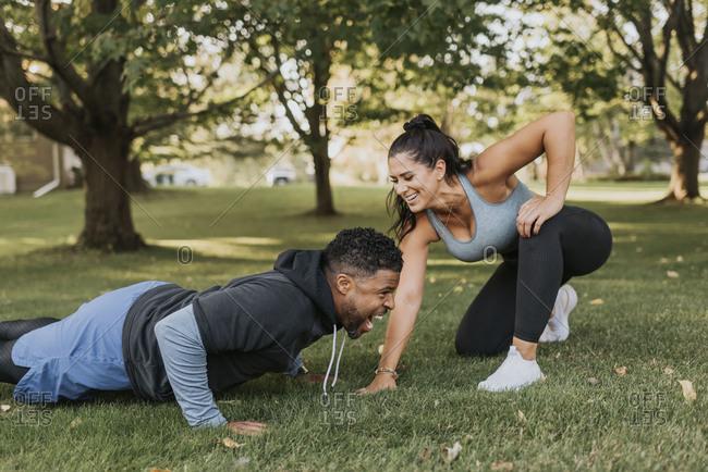 Smiling woman looking at man doing push up at backyard