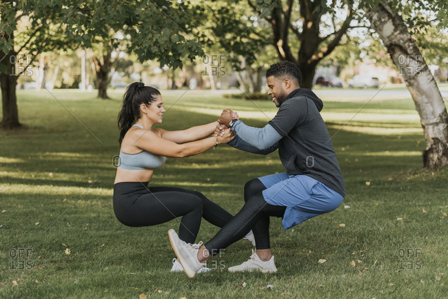 Couple holding hands while doing crouching exercise together at backyard