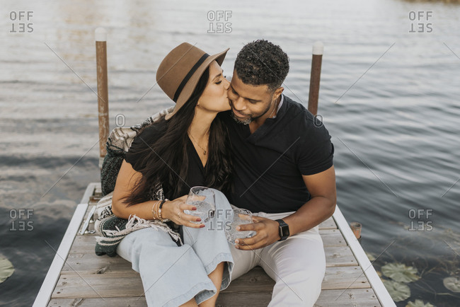Woman with wineglass kissing man while sitting on pier