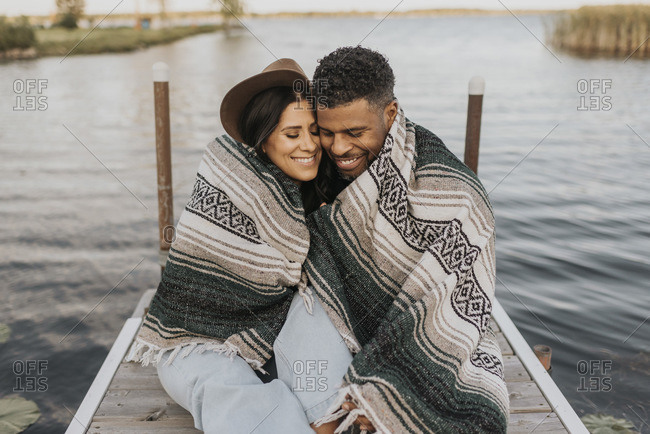 Smiling couple covered in blanket sitting on pier against lake