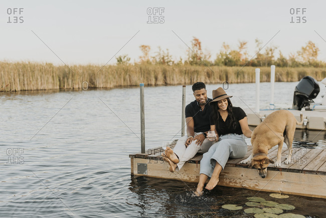 Smiling couple sitting with dog on pier