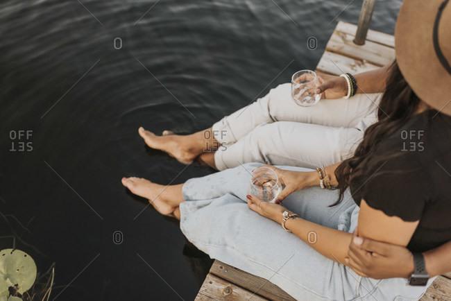 Boyfriend and girlfriend drinking wine while sitting on pier