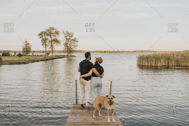 Dog standing by couple on pier against lake
