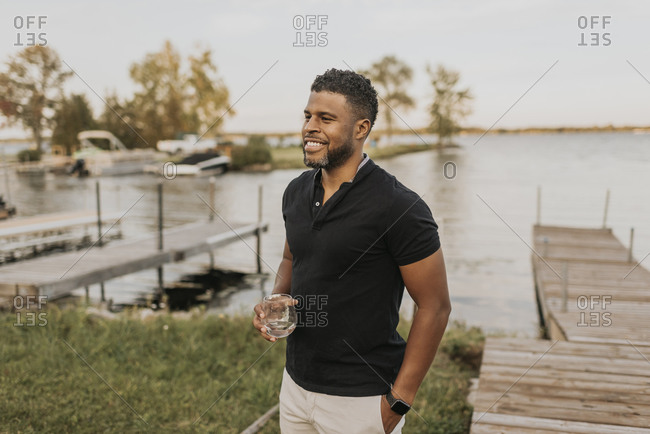 Smiling man standing with wineglass and hand in pocket by pier