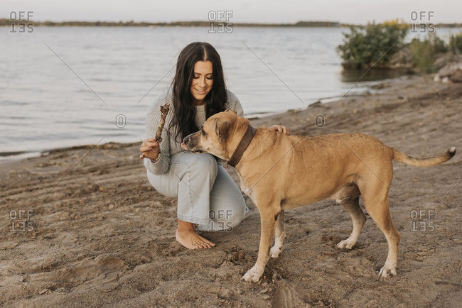 Woman playing with dog while crouching against lake during sunset